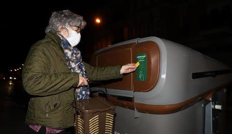 Una veïna de Pardinyes tira l'orgànica en un dels contenidors amb la seua targeta individual.