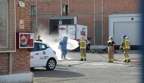 Bombers netejant l'equip de protecció d'un company.