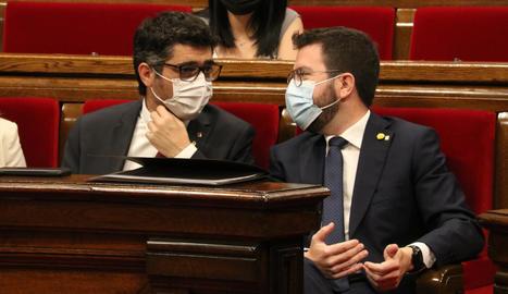 El president del Govern, Pere Aragonès, conversa amb el vicepresident, Jordi Puigneró, durant el ple al Parlament