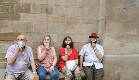 Veïns de Lleida fent el posat de treure's la mascareta al banc del 'si no fos' de la Paeria.
