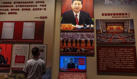 Un jove contempla un quadre de Xi Jinping en un museu.
