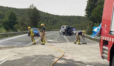 Bombers netejant la carretera, que va estar unes tres hores tallada, i al fons un dels turismes implicats.