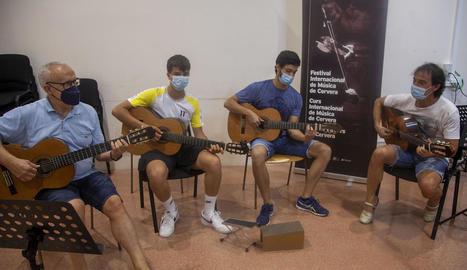 El professor de guitarra Xavier Gómez, ahir amb tres dels alumnes del curs de música de Cervera.