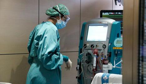 Un malalt és atès per una infermera a l'UCI de Vall d'Hebron.