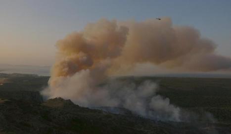 Un helicòpter sobrevolant ahir la zona del massís del Montgrí afectada per l'incendi.