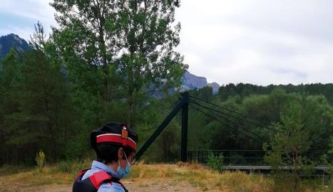 Un agent dels Mossos d'Esquadra al costat de la foguera.