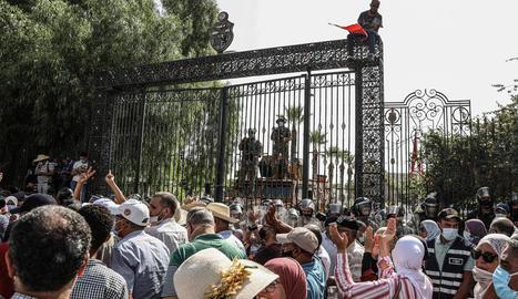 Soldats tunisians a la porta del Parlament davant de les protestes de ciutadans per la seua suspensió.