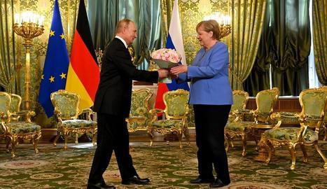Putin entrega un ram de flors a Merkel, ahir a Moscou.