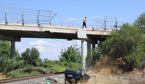 El vehicle va trencar la tanca de seguretat i va acabar bolcat al voral de les vies del tren.