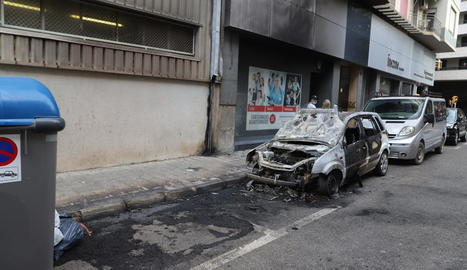 Estat del cotxe calcinat i de la façana danyada al carrer Riu Ter.