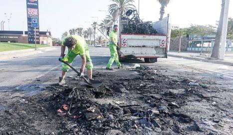 Operaris de la neteja retiren restes calcinades durant l'últim macrobotelló a Barcelona.