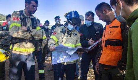 Els equips de rescat consultant un mapa ahir abans que es trobés el nen.