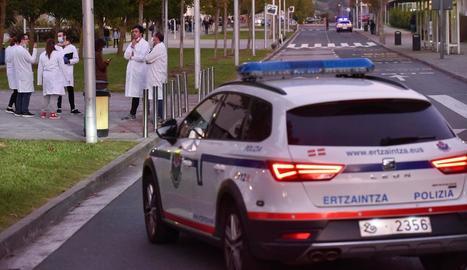 Un cotxe de l'Ertzaintza i diversos alumnes, davant la facultat de Leioa on va tenir lloc el tiroteig.