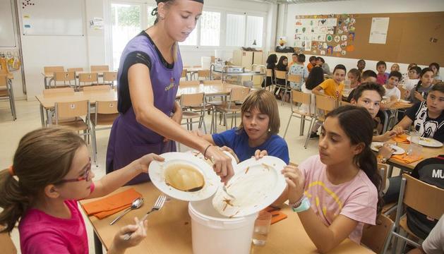 Els alumnes llancen en un cubell el menjar que els ha sobrat.