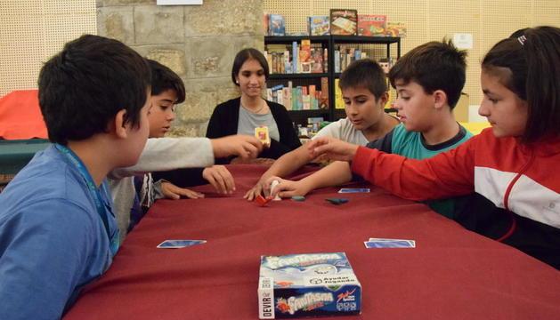 Nens jugant a un dels jocs de taula (esquerra) i altres participants escollint entre les múltiples propostes.