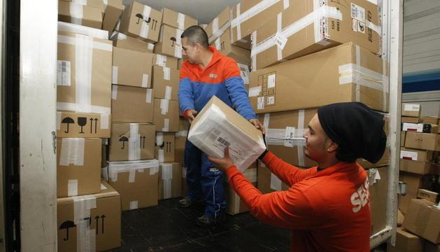 Operaris carregant paquets en un dels camions de repartiment de Seur.