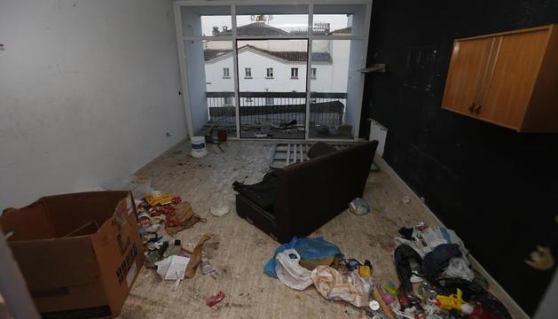 El menjador d'un dels pisos, destrossat i ple d'escombraries i brutícia.
