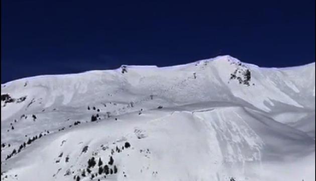 Imágenes de la secuencia de la avalancha y cómo la esquiadora (señalada en rojo) queda cubierta por la nube de polvo de nieve el pasado jueves en Baqueria Beret.