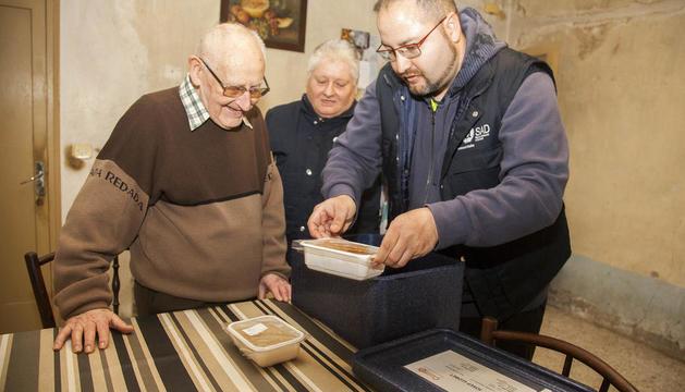 Miquel Àngel i Francisca de Alba entregant el menjar a Josep de 86 anys i que viu sol.