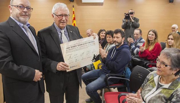 Queraltó, al costat de l'alcalde, mostra el document que l'acredita com a fill predilecte de Vallbona.