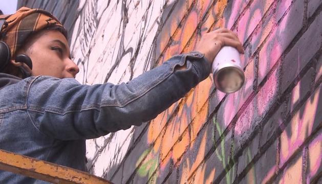 Una artista pintando un mural en el festival GarGar de Penelles.