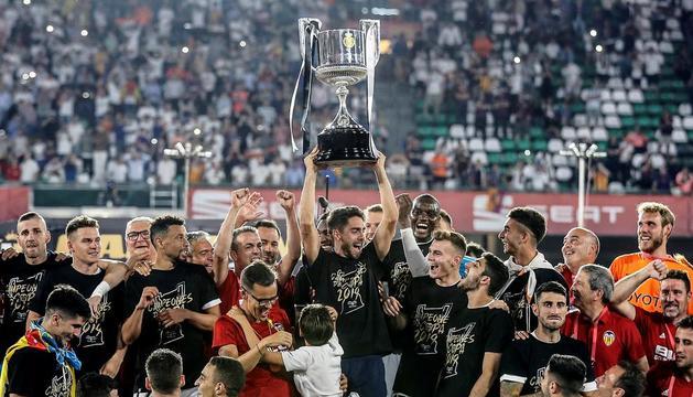 Jugadors del València aixequen la Copa que li van guanyar ahir al Barcelona, a la final disputada al Benito Villamarín.