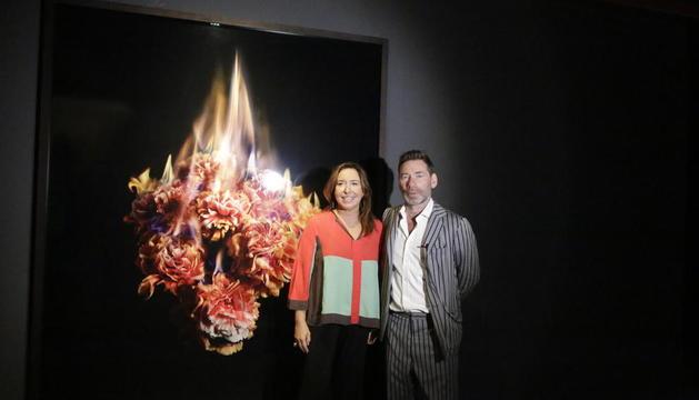 La directora de la Fundació Sorigué, Ana Vallés, i Mat Collishaw, al costat d'una obra de flors 'en flames'.