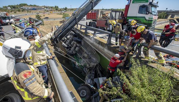 Diez dotaciones de bomberos trabajan para excarcelar el conductor de un camión que ha caído al canal de Balaguer en Alcoletge