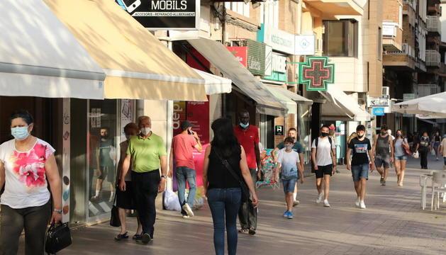 Diverses persones passegen amb mascareta a l'Eix de Lleida, ja que encara és obligatòria a l'aire lliure.