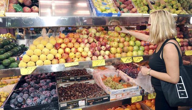 Foto d'arxiu d'una dona comprant fruita en un supermercat.
