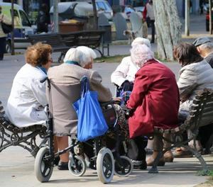 Un grup de jubilats asseguts en un banc de la ciutat de Lleida.