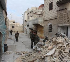 Soldats sirians caminen per un carrer d'Alepo després d'una batalla.