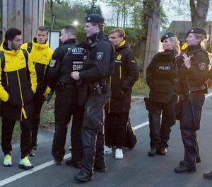 Jugadors del Borussia Dortmund, al costat de policies fortament armats després de l'atemptat contra l'autobús de l'equip.