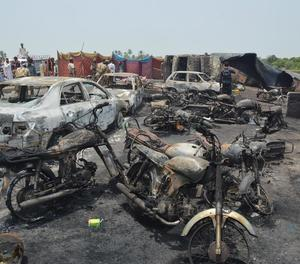 Cotxes i motos calcinats al lloc on va explotar el camió carregat de gasolina al Pakistan.