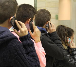 Joves amb telèfon mòbil.