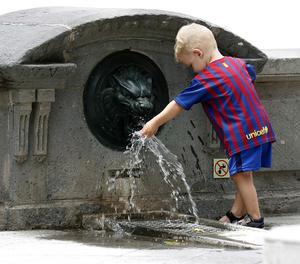 Un nen juga amb l'aigua d'una font.