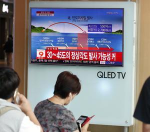 Ciutadans sud-coreans miren la notícia del llançament del míssil de Pyongyang.