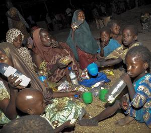 Una família nigeriana menja la seva ració d'aliments en un campament de desplaçats interns a Maiduguri