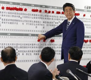 El primer ministre japonès, Shinzo Abe, posa un pin en forma de rosa al nom dels candidats.