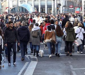 Ciutadans en un carrer comercial.