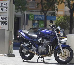 Una motocicle estacionada en una gasolinera.