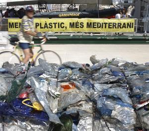 Un vaixell de l'organització Greenpeace al port de València davant d'un munt de bosses de plàstic.