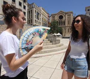 Dos joves poloneses intenten apaivagar la calor a la plaça Sant Joan de Lleida.