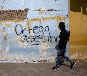 Un jove amb la cara tapada camina davant d'una pintada a Nicaragua.