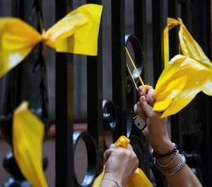 Una persona retira llaços grocs.
