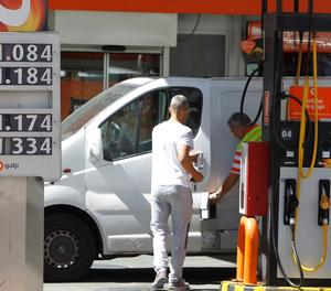 Una furgoneta reposta combustible en una gasolinera.