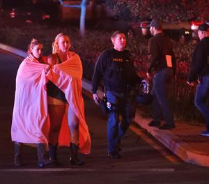 Dues dones embolicades en un llençol abandonen l'àrea del tiroteig a prop del bar Borderline a la localitat de Thousand Oaks, Califòrnia, Estats Units.
