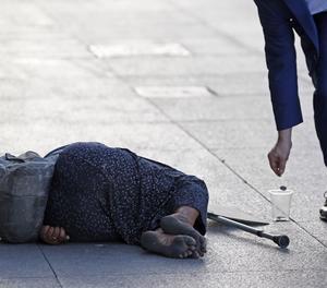 Una home llança una moneda a una dona que practica la mendicitat.