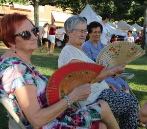 Un grup de dones miren d'evitar la intensa calor amb vanos.