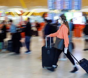 Una viatger amb mascareta en un aeroport.